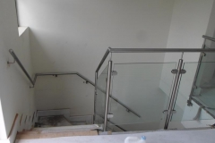 Stainless-steel-handrail-along-wall-guides-the-user-away-from-the-staircase-bend