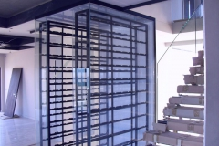 Custom-steel-and-glass-wine-rack-which-act-as-a-divider-between
